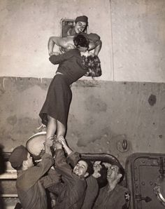 New York, 1945 - Actress Marlene Dietrich is hoisted up to kiss a GI as he arrives home from World War II.