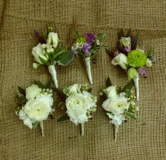 Wedding boutonnieres  A cluster of ranunculus spray roses and wax flowers, green buttons and veronica