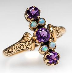 This intriguing antique victorian north to south ring features natural amethyst and opal gemstones. This antique ring is crafted of solid 9k yellow gold and is over 100 years old.