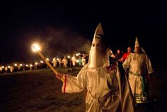 """In this Saturday, April 23, 2016 photo, members of the Ku Klux Klan participate in cross burnings after a """"white pride"""" rally in rural Paulding County near Cedar Town, Ga. Born in the ashes of the smoldering South after the Civil War, the KKK died and was reborn before losing the fight against civil rights in the 1960s. Membership dwindled, a unified group fractured, and one-time members went to prison for a string of murderous attacks against blacks. Many assumed the group was dead, a…"""