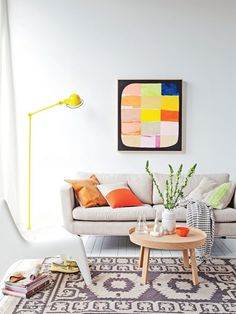 A small simple round coffee table in a colorful and open living room.