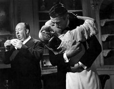 "Alfred Hitchcock sneezing while Ingrid Bergman and Gregory Peck kiss on the set of ""Spellbound"" 1945"