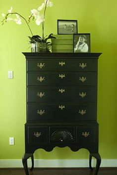 A vintage highboy dresser with seven drawers features curved legs, dark pewter hardware and a seashell design carved into the bottom center drawer.