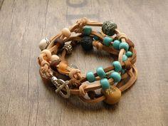 Inangahua - náramek z korálků Dámský etno náramek z keramických, hliněných a skleněných korálků. Na zápěstí se navine ve čtyřech otočkách. Náramek lze nosit i jako náhrdelník. Materiál a komponenty: Základem náramku je semišová kůže v hnědé a béžové barvě. Komponenty jsem použila hliněné a keramické ručně vyrobené korálky, skleněné a kovové korálky. ...