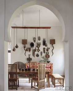 The dining table is surrounded  by custom-made chairs  inspired by Charles Rennie Mackintosh and Frank  Lloyd Wright; horn sconces flank a collection of  African masks, and the suzani  is from Uzbekistan.