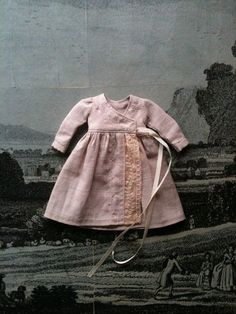 This pretty wraparound dress is made from a delicate dusky pink cotton with vintage lace details. It ties with a vintage silk ribbon and can be