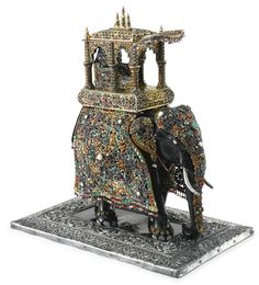 AN INDIAN PARCEL-GILT AND GEM-SET CARVED WOOD FIGURE OF A CAPARISONED ELEPHANT, LATE 19TH - EARLY 20TH CENTURY the ebonized wood elephant covered with rich caparison mounted in pearls and cabochon rubies, emeralds, sapphires, opals, turquoise, carnelian, garnets, and yellow beryls, trimmed with matching beads, the howdah fitted with a seated dignitary, on silver-covered rectangular base