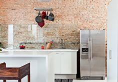 Os ladrilhos hidráulicos em dois tons diferentes de cinza cobrem o piso e sobem pela parede até a bancada de granito andorinha, ao lado do fogão e de outros acessórios de cozinha industrial. As panelas ficam expostas e conferem um ar descontraído. Projeto de Gustavo Penna