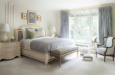 Touches of gold are woven throughout Suzanne's bedroom, from the detail on the bed to the base of the table lamp to the ornate frame of the upholstered bench.