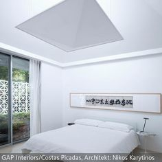 Der asiatisch-minimalistische Look des Schlafzimmer gibt ihm eine entspannte Wirkung. Indirekte Beleuchtung an der Decke und ein Bett mit schmalen Bettfüßen, das …