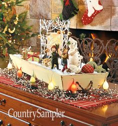 Take a long wooden box or trencher and use it to create a tabletop display that includes a tree-like candleholder, seasonal figures, small packages and holiday lights. Christmas Ideas, Christmas Wreaths, Christmas Crafts, Christmas Decorations, Table Top Display, Display Ideas, Country Sampler Magazine, Primitive Country Christmas, Holiday Lights