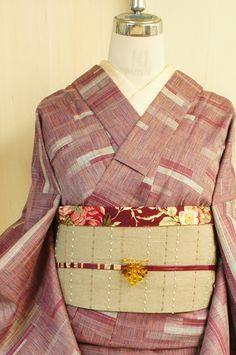 ラズベリーのような紫紅色に、リボンテープのようなモダンジオメトリックデザインが織り出されたウールの単着物です。