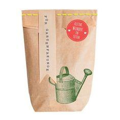 Wundertüte Gartengeschenk. Eine mit einem Gartenmotiv bedruckte Tüte gefüllt mit Samen und Kokos Quelltablette für alle Menschen mit dem berühmten grünen Daumen.