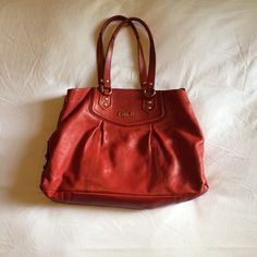 Coach 'Ashley' Leather Carryall Gorgeous bright red color with gold hardware. 100% authentic, purchased from the coach website in early 2014 and carried only about 10x. Features multiple interior pockets, and is roomy enough to carry a MacBook Pro (snugly) or an ipad/netbook with ease. Lining has a few small stains and a mark where a bottle of superglue leaked in my purse (ugh) but is in otherwise excellent condition. Adjustable, remove able red leather shoulder strap included. I hope you'll…