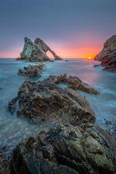 Bow Fiddle Rock at sunrise on the Moray Coast in Scotland.