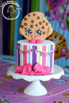 """7"""" cake with stripes, bow, and banner. Kooky Cookie was was made using Wilton fondant."""