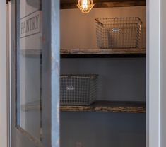 3015731ce826 Vintage style pantry door opening to reveal stained wood floating shelves  lined with wire baskets illuminated by a caged edison bulb pendant.