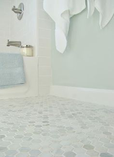 Serene bathroom makeover with hexagon floor tile and white subway wall tile, Sherwin Williams Sea Salt paint and crisp white details