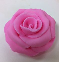 I'm getting the hang of making these roses out of just a single piece of gum paste. This one was made with some extra pink rolled fondant I had left over from class today, but I added a generous amount of Tylose to it first.