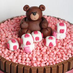 detalhe do bolo com ursinho e dadinhos feitos em pasta americana
