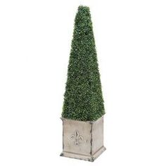 "Bring stately style to your foyer or home office with this stylish faux topiary, featuring a weathered planter and obelisk-inspired silhouette.  Product: Faux boxwood topiaryConstruction Material: PolyesterColor: Antique off-white and greenFeatures:  Obelisk-inspired silhouetteWeathered planterFade resistant Dimensions: 52"" H x 13"" W x 13.5"" D"