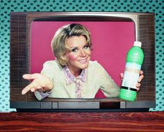 Woman holding domestic product emerging from television…