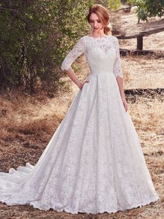 Maggie Sottero - CORDELIA, This vintage-inspired wedding dress features allover lace with sheer lace comprising the three-quarter sleeves, bateau neckline, and square back. Softly scalloped trim completes the unique glamour of this ballgown. Complete with pockets at the hip and finished with covered buttons over zipper closure.