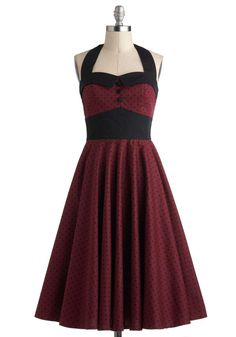 Details & Measurements Singing at venues across the country, you'll need a look that's as bold as your vocals - don this dress, and your performance will be unforgettable! Noir dots harmonize with a beautiful burgundy hue to create a sassy style that's sure to charm the toughest crowds. You'll send audiences swooning when you start crooning in the pin-up style, buttoned bodice and halter neckline. Accompany this look with woven peep toes, a cuff bracelet, and a black fascinator, and you'll…