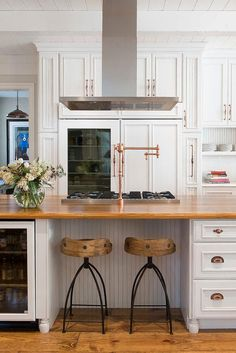Stunning kitchen features white raised panel cabinets adorned with copper hardware framing a glass door refrigerator.
