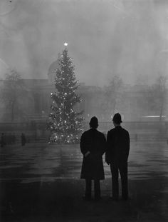 Two policemen regard London's 64ft Christmas tree, a gift from Norway, illuminated in Trafalgar Square, in front of the National Gallery, 1st December 1948.
