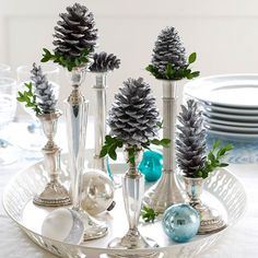 Instead of topping silver candlesticks with the expected, try placing a painted pinecone on top. Fill a round tray with candlesticks in a variety of sizes, and finish with a scattering of glass ornaments for a easy and simple centerpiece.