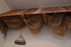 antique shop dis[lay with burlap | Decorative corrugated metal awning with burlap and light fixtures.
