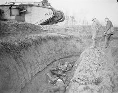 BATTLE CAMBRAI 20-30 NOVEMBER 1917 (Q 7851) An immobilised British Mark IV tank stands at the lip of a captured German trench at Flesquieres, in the bottom of which lie four dead German soldiers.