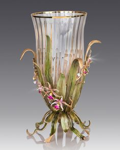 Handcrafted vase. Mouth-blown optic glass with golden rim. Metal orchid-leaf base hand enameled and hand set with Swarovski crystals. May be uses as hurricane for pillar candle or as a vase. Glass can