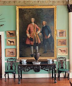 Hall at Glin Castle, County Limerick. An Irish mahogany serving table with the FitzMaurice and Moore arms, ca.1750, flanked by a pair of Irish mahogany dining chairs, ca.1750. The portrait by Heroman van der Mijn (1684-1741), ca.1740, is of John FitzGerald, 12th Knight of Glin being handed a challenge to a duel. Photography by Dara McGrath.