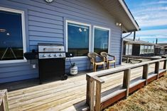 Large ocean facing wrap around deck with patio chairs and a gas BBQ