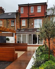 The back of this terrace house is gorgeous, and is totally celebrated by the style, the wooden deck and chairs and the side garden. Gorgeous.