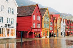 Bergen. The colourful buildings of Bryggen stand in stark contrast to the  bleak landscape surrounding them.  Bryggen is a series of Hanseatic commercial buildings lining the  eastern side of the fjord coming into Bergen, Norway. Bryggen has  since 1979 been on the UNESCO list for World Cultural Heritage sites. Photo: John & Tina Reid