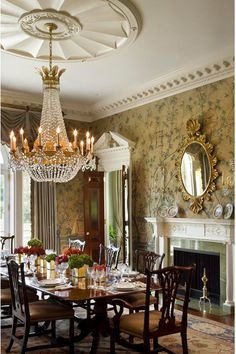 THE FORMAL DINING ROOM OF A BEAUTIFUL NEW HOME, DESIGNED BY ALLAN GREENBERG ARCHITECT AND INTERIOR DESIGNER ELISSA CULLMAN. THE LUXURY HOUSE WAS FEATURED IN THE OCTOBER 2009 ISSUE OF ARCHITECTURAL DIGEST MAGAZINE. AN ELEGANT CHANDELIER HANGS ABOVE THE MAHOGANY DINING TABLE. OTHER ACCENTS IN THE ROOM INCLUDE A FIREPLACE WITH AN ELABORATE MANTLE AND 18TH CENTURY HAND-PAINTED WALLPAPER.