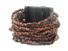 Dualismo beaded cuff bracelet - Bring out your two best sides and celebrate the beauty of duality and contrast with this stunning 14 rows, 2 toned bracelet made of vivacious orange and enigmatic black glass beads, brought together with a stylish wooden cuff with its signature... View this Product