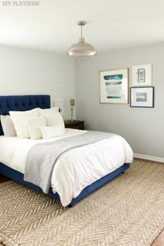 A navy headboard, neutral jute rug, and white bedding make for a winning bedroom look. Love this calming gray master bedroom decor. Plus that wall art is perfect!