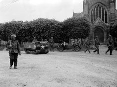"""Soldiers and U.S. vehicles traveling on the role of the church of Sainte-Marie-du-Mont (Utah Beach area). An M-29 Weasel's HHQ Co, 8th Inf. Rgt of the 4th Inf. Div. US. Basically a Policeman, next to a Jeep. Photo taken on June 7 by the war are Kaye. According Historica No. 79 page 128, Heimdal Editions, 2004, the photo """"shows the 3/502nd PIR of the 101st AB starting to US-Blosville Houesville, specifically the H Co T / 5 Robert Marois facing the the objective. """""""