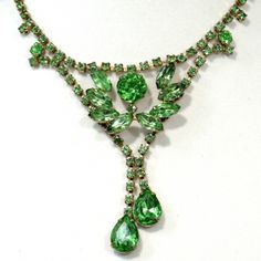 Dangling Goldtone Necklace with Green Rhinestones. Marvelous unsigned beauty that has a great design. In good vintage condition with all stones present.