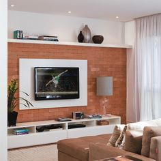 """Esta sala de TV de 15 m², assinada pela arquiteta Anna Parisi, foi pensada para que uma mãe e sua flha adolescente pudessem se esparramar e ficar juntas. De verdade: o sofá convencional foi substituído por duas chaises grudadas, repletas de almofadas. """"Resolvido o aspecto do conforto, tratei de produzir uma atmosfera luminosa e bem feminina para as duas. Daí o uso do branco na marcenaria e a parede coberta de tijolos, cuja textura passa uma sensação calorosa"""", explica a arquiteta. O…"""