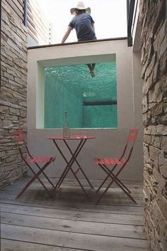 Une petite terrasse se trouve en contrebas de la maison. L'un des côtés de la piscine, équipé d'un mur de verre, permet de voir le spectacle de ceux qui piquent une tête.