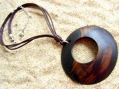 Colgante Kalahari. Ebano. Ligero colgante de forma redonda en madera de ébano. Cuero marrón a juego y cadena rolón, con baño de plata, para que puedas ajustar el colgante a tu gusto.