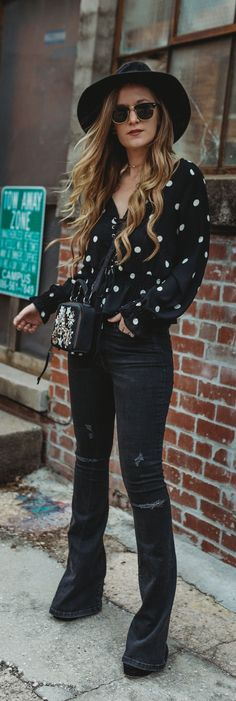 Boho spring outfit styled with a polka dotted lace up top, black flared jeans, and jeweled crossbody #bohooutfit #flaredjeans