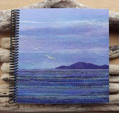 Sketchbook with printed cover featuring one of my own felt landscape pictures. This is a high quality professionally printed and coil bound sketchbook. Measures 21 x 21 cm and includes 50 sketchbook quality paper pages. The quality of the print makes t. Textiles Sketchbook, Sketchbook Cover, Sketchbook Ideas, Seascape Art, Machine Embroidery Projects, Textile Art, Textile Design, Small Quilts, Pretty Art