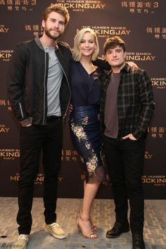 Josh Hutcherson, Jennifer Lawrence and Liam Hemsworth pose for photographers at the 'Mockingjay Part 2′ press conference in Beijing, China