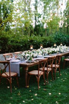 Garden wedding reception decor idea - long, wooden tables with light blue table runners, greenery + white flower centerpieces and twinkle lights {Megan Clouse Photography}
